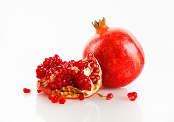 Ripe tasty fresh red pomegranate fruit and its grain with reflection on a light background. Studio shot.