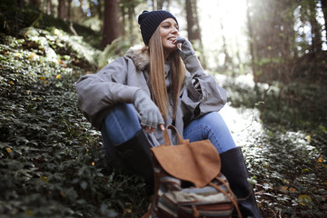 Smiling young woman sitting in forest