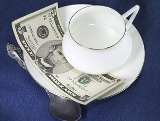 Empty porcelain white cup with teaspoon on white porcelain saucer, five dollar banknote under the cup as a lavish tips. On blue cotton background.