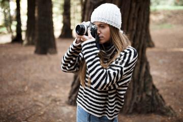 Stylish female taking photos in wood