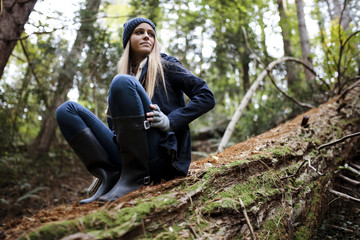 Woman in warm clothing sitting in woods