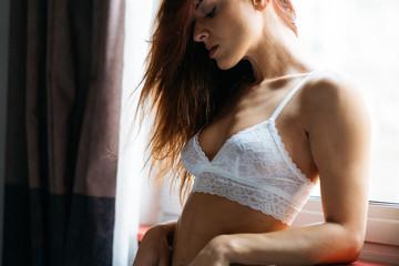 Female in white bra bending on window