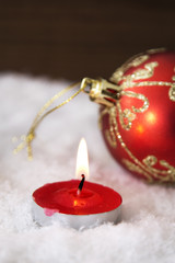 card of Christmas with candle and balls of Christmas in the snow