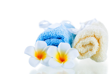 terrycloth towels and tropical flowers isolated on white backgro