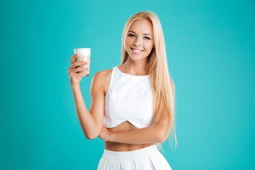 Smiling blonde woman with long hair drinking coffee to go