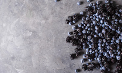 Blackberries, blueberries a gray abstract background. Copyspace. Healthy food concept.  Colorful festive still life. Loosely laid berries in different positions