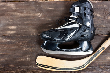 Overhead view of hockey stick and ice skates on old rustic woode