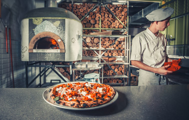 Wall Mural - young male cook cooked pizza in restaurant