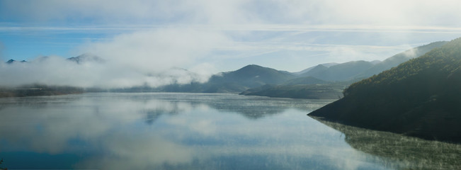 Mist rising over a reservoir in a mountainous landscape.