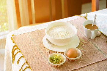 Fototapete - rice porridge, rice gruel or congee with pork, egg, sliced ginger and vegetable, delicious the traditional Chinese breakfast on wooden table and hot coffee