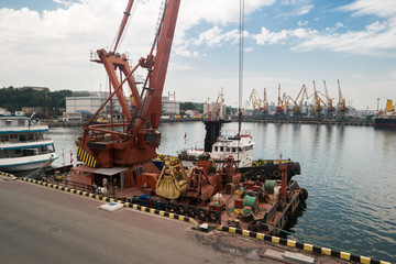 Crane on the pier. Port at daytime. Heavy and durable. Maintenance of ships.