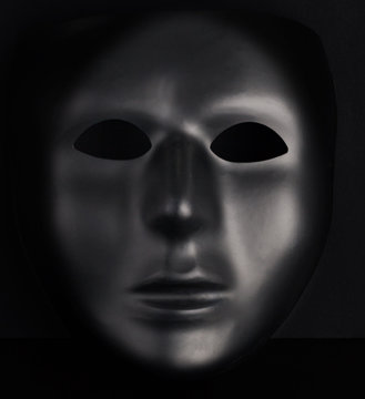 Anonymous black mask protruding from pitch black background. Anonymity concept