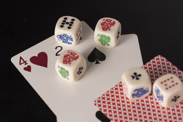 Gaming dice with cards on dark table