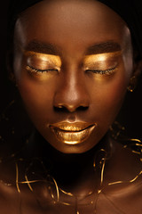 Close up portrait of beautiful african woman with creative gold make–up and jewelry