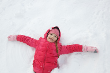 Playful girl playing in snow, making a snow angel