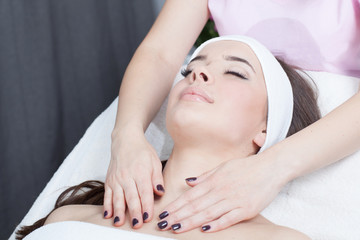 Beautiful young woman receiving facial massage with closed eyes in a spa salon