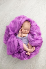 sleeping newborn girl on a pink wool background, close-up