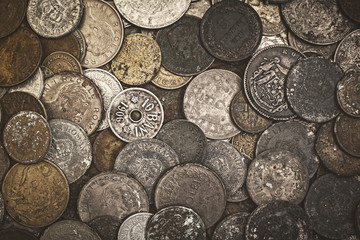 Old oxidized coins of different nationalities from different periods, top view.