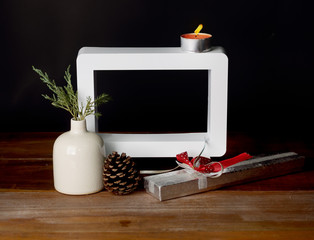 Christmas gift with empty picture frame on wooden table