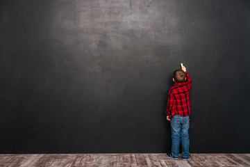 Little child standing near blackboard and drawing on it