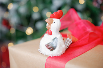 the symbol of the new 2017 rooster on the background of Christmas tree and boxes with gifts