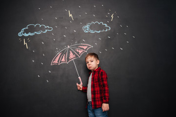 Sad kid holding umbrella on the chalkboard with drawings