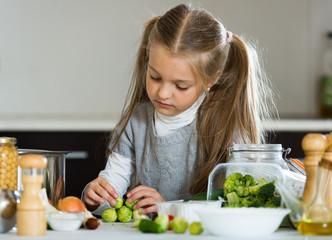Cute little girl cooking veggies in kitchen