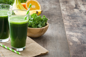 Kale smoothie with banana and orange on wooden background