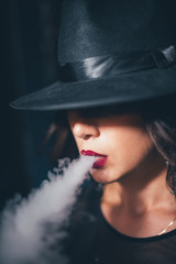 beautiful girl in a black dress smokes hookah on background chains