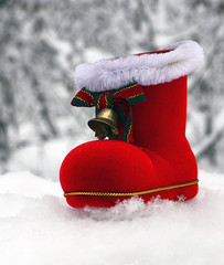 Christmas Santa boot with bell on winter snowy forest background.Winter holidays,Merry Christmas or Happy New Year concept.Selective focus