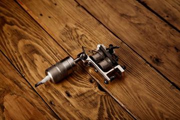 Metal handmade classic induction tattoo gun on rough brown table
