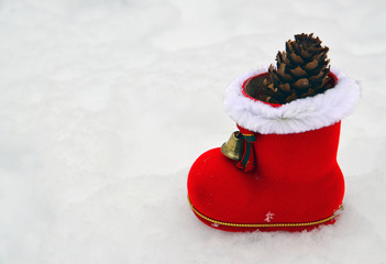 Christmas Santa boot with fir cone on white snow background.Winter holidays,Merry Christmas or Happy New Year concept.Selective focus,copyspace