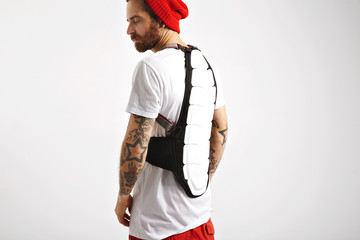 Serious bearded and tattooed snowboarder in white t-shirt and red beanie wearing white and black back protector isolated on white