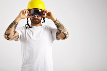 Serious focused young man in snowboarding helmet and unlabeled white t-shirt putting on goggles looking straight into the camera in studio with white walls