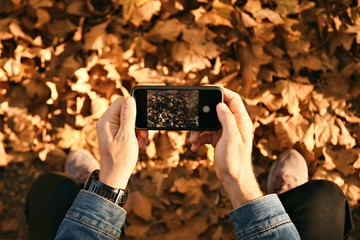 Man wearing denim jacket takes a picture of autumn leaves on his smartphone, close up shot