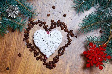 Christmas composition of straw Christmas decorations in white with coffee beans in shape of heart on wooden background