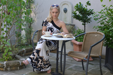 Blonde woman in an elegant dress sitting at a garden table and writing down in her notepad