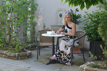 Woman in an elegant dress sitting at a table in a lush garden and writing in a notepad