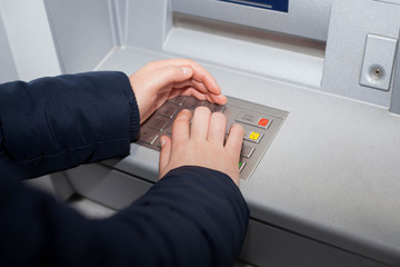 Woman hand writing password for her bank account at ATM (color t