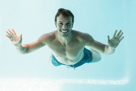 Smiling shirtless man swimming underwater