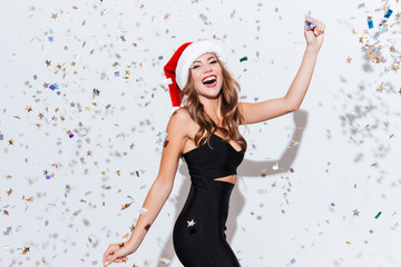 Happy excited woman in santa claus hat dancing and laughing