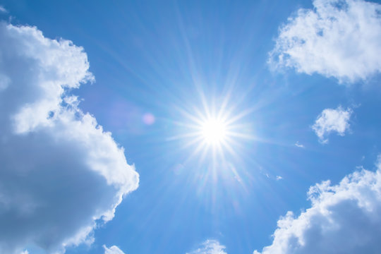 Realistic shining sun with lens flare on blue sky clouds nature day sky background