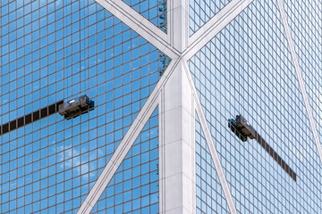 Work platforms hanging by ropes on the side of a skyscraper