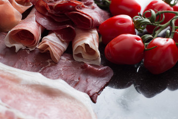 Ham mix. jambon. Traditional Italian and Spanish salting, smoking, dry-cured dish - jamon Serrano and prosciutto crudo sliced with herbs and tomatos on dark stone background. Copy space. Closeup.