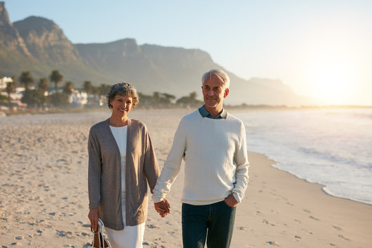 Happy senior couple taking a walk on the beach together