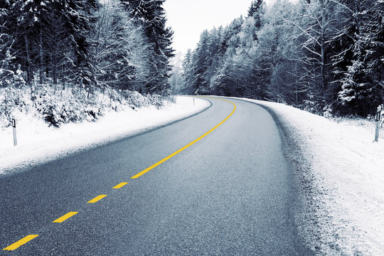 Empty country road in snowy forest in winter