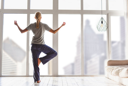 Relaxed young woman exercising at home
