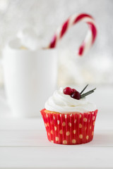 Homemade Xmas cupcakes with cranberry and rosemary on white wooden background