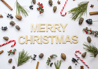 MERRY CHRISTMAS made of wooden letters decorated with star anise, pine cones, sweets, nuts, pine branch on white background. Creative concept