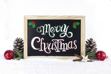 """Chalkboard with Christmas decoration on snow white isolated background, and text """"Merry Christmas"""" written on it."""